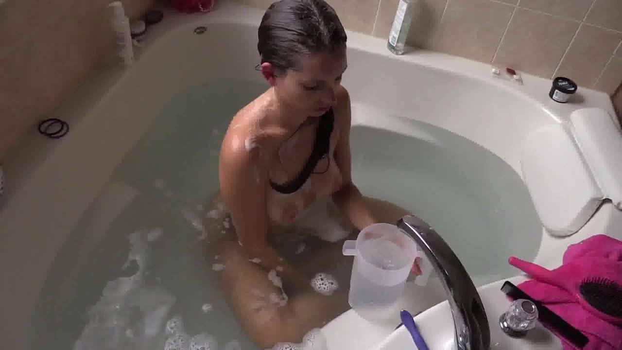 Милая брюнеточка принимает ванну и дергает себя за сиськи