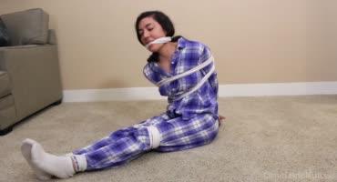 Тёлка в пижаме связана на полу и барахтается в неволе