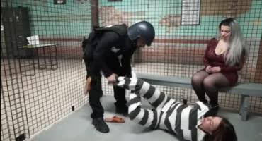 Шлюха смотрит на мучения скованной арестантки