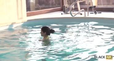 Молодая брюнетка купается в бассейне и отсасывает черный член
