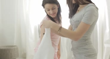 Молодые девушки после школы играют на кровати