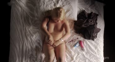 Аппетитная милашка развлекается на кровати с игрушками