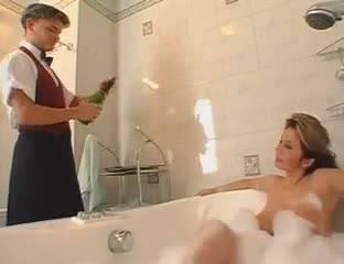 Грудастая тетка трахает в ванной молодого паренька