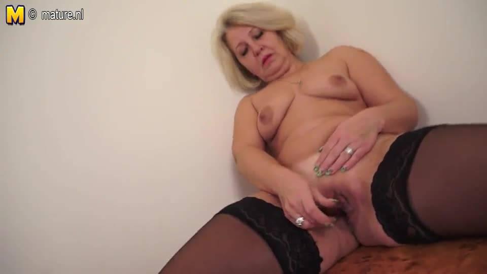 Зрелая мадам, в чулках и чёрном нижнем белье, мастурбирует на кровати